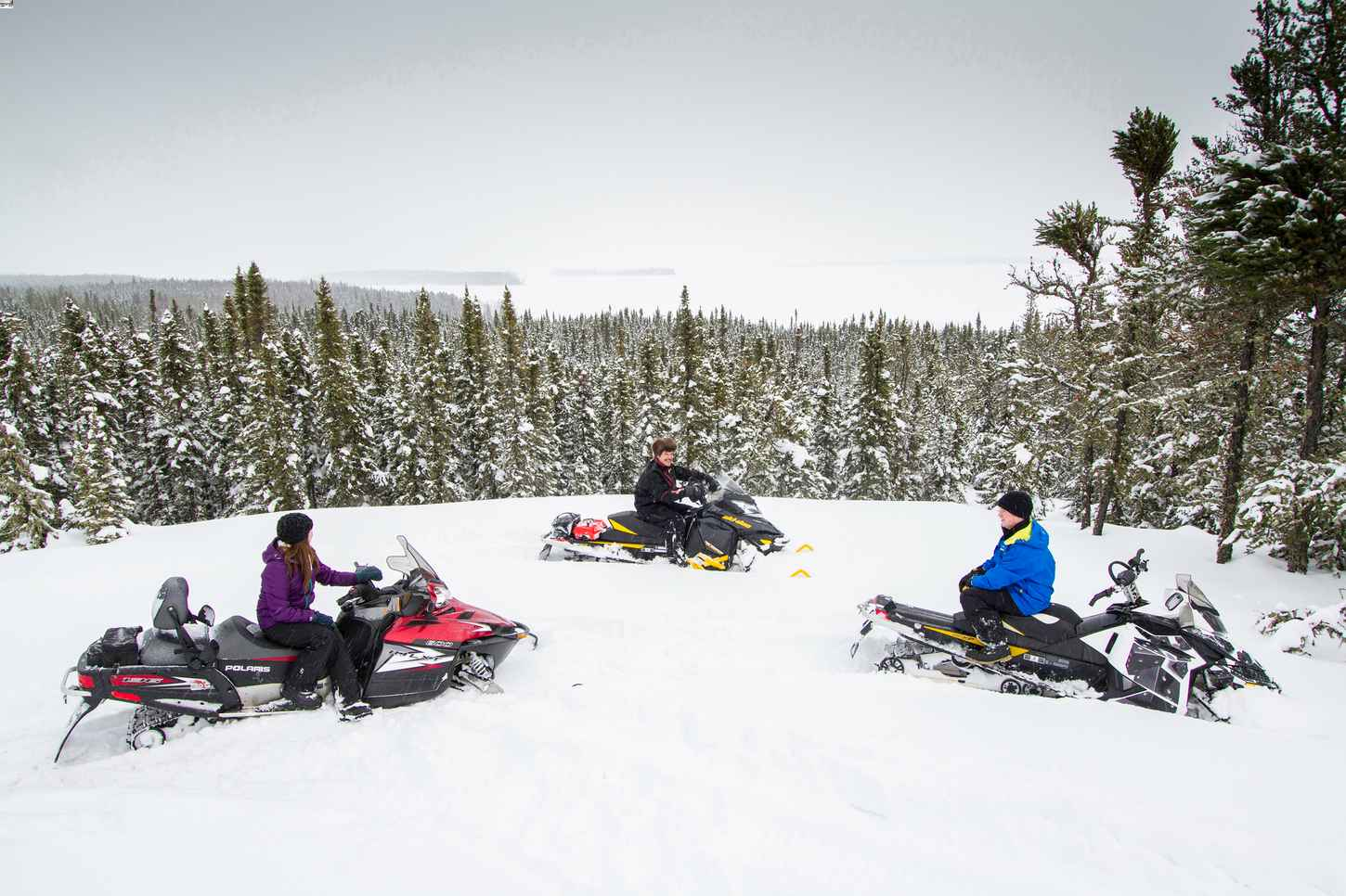 Three people on snowmobiles at Lac LaRonge Provincial Park in Saskatchewan